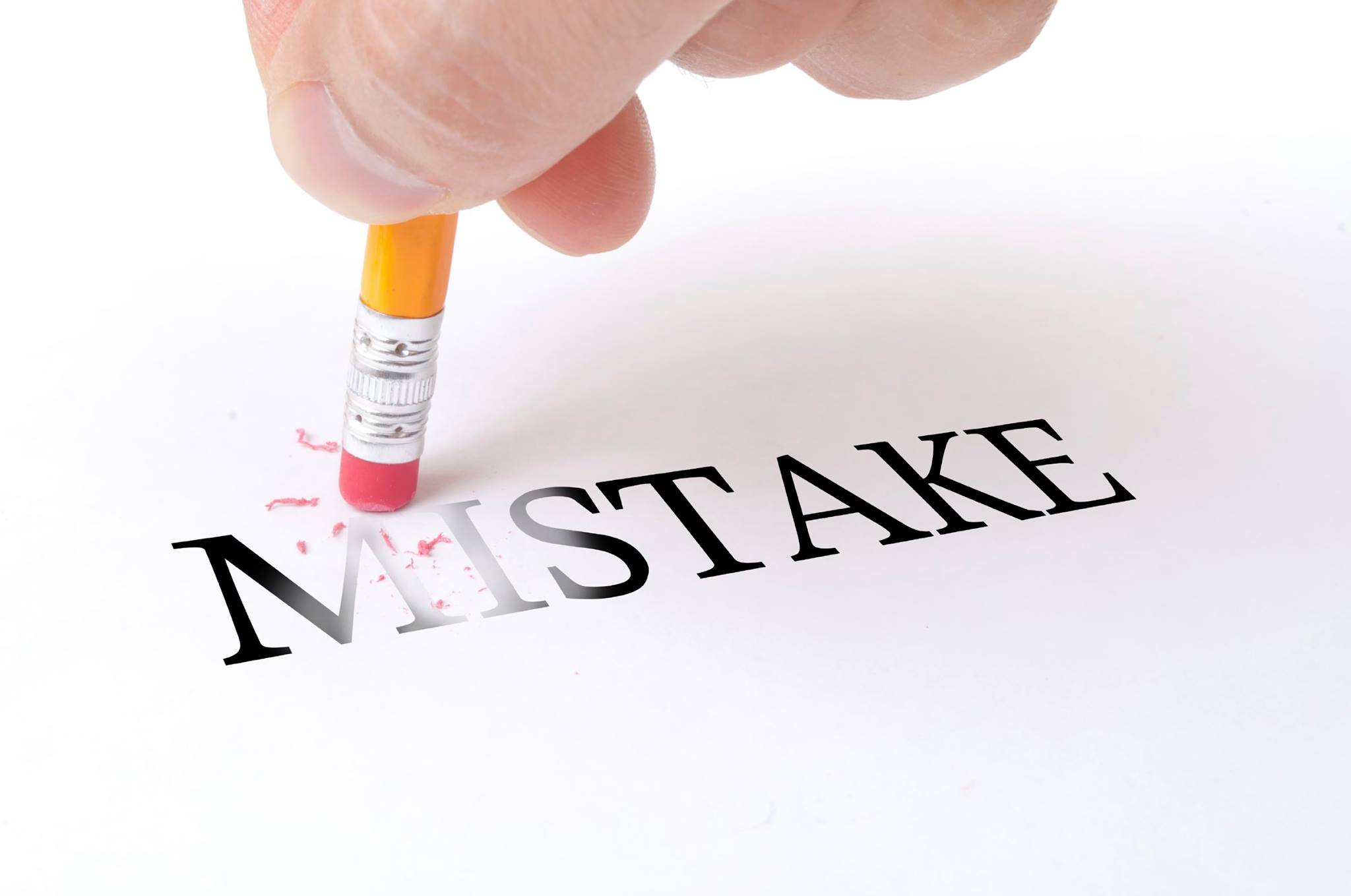 "Male hand holding wooden pencil and delete word ""MISTAKE"" on the white paper"
